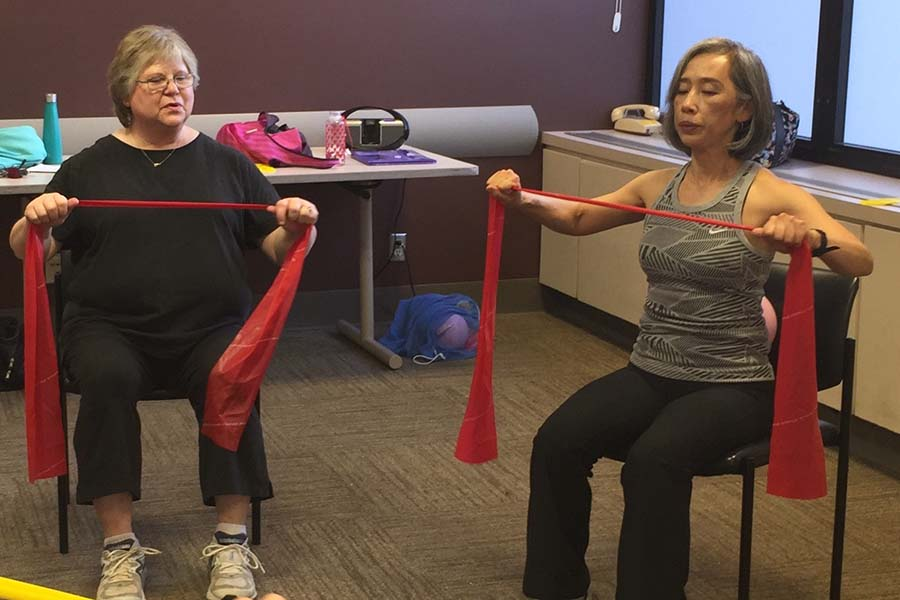 older women exercising with bands