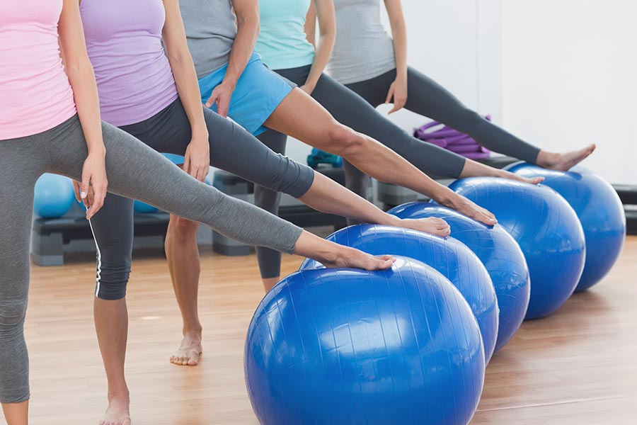 pilates students lined up with feet on exercise balls