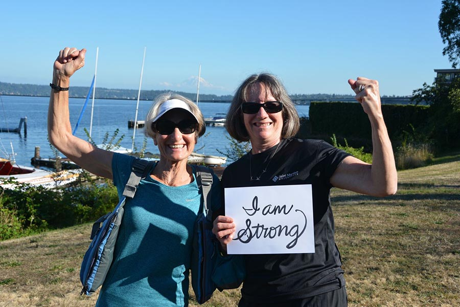 two female cancer survivors raising their fists by the dragon boats